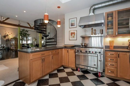 I love everything about this space! The chef's stove and vent, the cabinetry, the black and white tile, and the spiral staircase!!!
