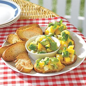 Avocado and Mango Salsa Crostini: 1 long, thin baguette   1/4 cup olive oil   Salt and pepper   1 large avocado, pitted, peeled and cubed   1 cup diced mango   2 tablespoons chopped fresh cilantro   1/2 small onion, finely chopped   2 tablespoons lime juice