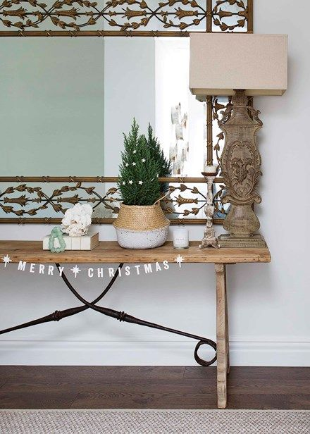 A Coco Republic console table is teamed with an enormous mirror and oversized lamps from US company Currey & Co. Festive cheer welcomes guests via a festive garland from Papier D'Amour   Home Beautiful Magazine Australia