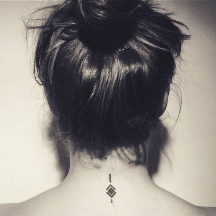 Small back of neck tattoo of a symbol on Astrid, to remind her to always keep a young spirit, stay foolish and have a positive attitude.