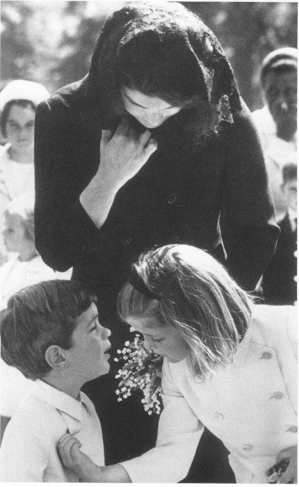 May 29, 1964: Caroline slips a small pin from John's coat as they and their mother visit John F. Kennedy's grave on what would have been his 47th birthday. John left the pin on the grave as a token of love.