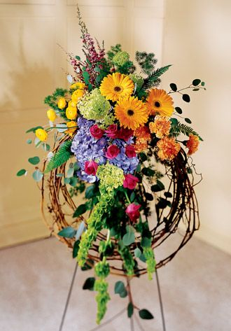 This rustic wreath uses gerbera daisies, roses, hydrangea and other blooms to express a vision of a country field. Appropriate to send to the funeral home. Arrangement is delivered with an easel for display.