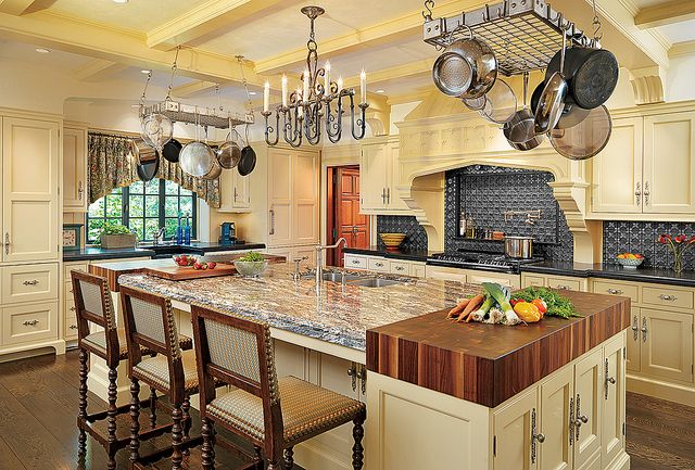 Yellow country kitchen with black tile and counters, and island with butcher block ends, and gray veined granite.