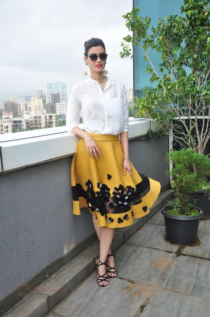 White shirt and mustard yellow skirt with black floral appliqué