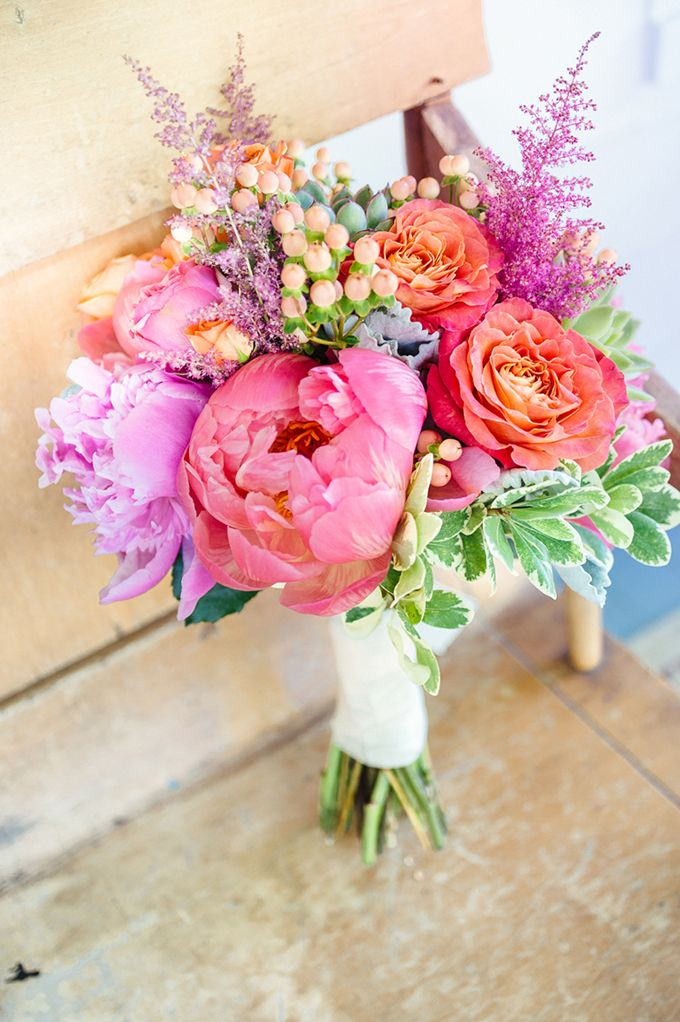 Bright wildflowers create a stunning bouquet for a whimsical outdoor #wedding.