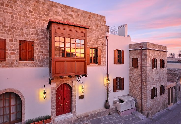 "EXCLUSIVE SUITES BOUTIQUE HOTEL. MEDIEVAL TOWN, RHODES, GREECE. -  The facade of our Hotel at sunrise, as seen from the top of the castle wall. The red door, the ""Sahnisi"" wooden balcony and the Roman sarcofagus turned into a fountain by one of the previous owners. -  kokkiniporta.com"