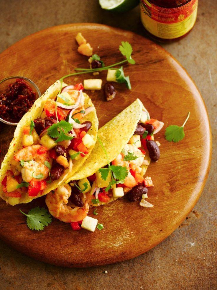 Bereiden: Verhit de olijfolie in een grote pan. Voeg de gehakte knoflook toe en laat goudbruin bakken. Voeg de garnalen toe en schep goed om. Breng op smaak met limoensap, chilisaus en peper. Blus voorzichtig met de tequila en flambeer. Breng extra op smaak met de gehakte koriander en meng. Om de pittige rode bonen te maken, fruit je de gesnipperde ui en de knoflook glazig. Voeg de komijn en de rode bonen toe en breng op smaak met chilivlokken en zout. Laat 5 min. sudderen.