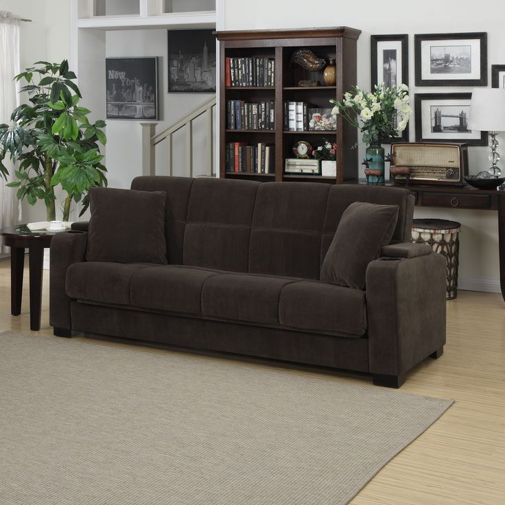 The Portfolio Tevin Convert-a-Couch features a transitional designed sofa sleeper with a storage area and cup holder built into each arm. The Tevin futon sleeper sofa is covered in a velvet like soft chocolate brown fabric.
