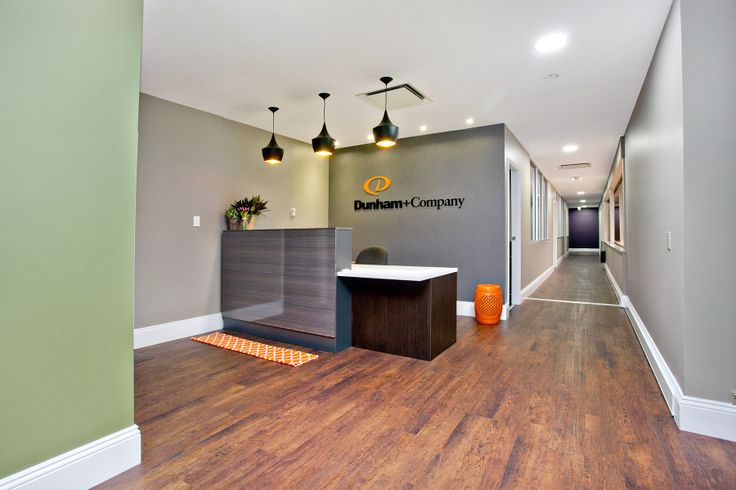 AFTER: Dunham and Company reception.  Floor is Expona by Polyfloor; custom designed desk; custom designed sign; full lighting design with LED and pendants.