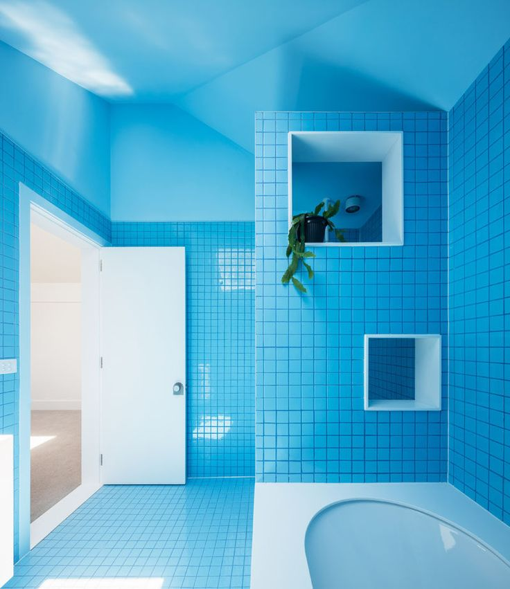 This modern bathroom features bright blue tiles on the walls and floor and a bright blue ceiling that keeps the space bright and fun. Square cut-outs on the wall next to the bath offer a place to store shampoos, soaps, and other bath essentials and help keep the area surrounding the tub clean and organized.