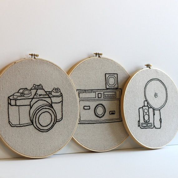 Product Description: One ten inch hand embroidered hoop art. Vintage camera embroidered with black thread on unbleached muslin. This design was hand drawn and embroidered by me. Fabric is permanently mounted in embroidery hoop. Inspiration: Hang on a wall or prop in a bookshelf as part of an eclectic photo collage. Great vintage inspired home decor. See my other vintage camera embroideries! Here: https://www.etsy.com/listing/119935791/vintage-camera-embroidery-hoop-art-hand Here: https...