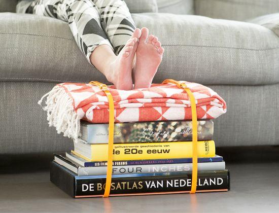 Heb je snel een extra zitplaats nodig maar geen krukjes meer in huis? Stapel dan flink wat (grote) boeken op elkaar, vouw daar een deken op en zet alles vast met twee (leren) riemen.
