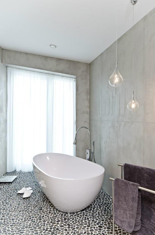 Koupelnu u hlavní ložnice zdobí vedle betonu a křehkých svítidel z foukaného skla i říční mozaika na podlaze.