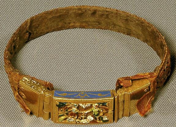 Armbånd i silke med emaljeret guldlås. Fundet i Henrik Vinds grav i Hjembæk kirke (død 1630). (Nationalmuseet)