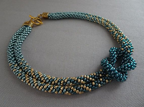 """Skillfully crafted, this stylish Ombre love knot necklace features two Kumihimo ropes in delicate gradients of soft seafoam, gold, and teal intertwined to form a knot, finished with a gold-tone toggle closure. Only Japanese seed beads are used for their high quality and uniformity. As a result, the necklace is smooth and flexible, and will conform nicely to your neckline. Dimensions: 18"""" x 1-1.5"""" x 0.5""""  Kumihimo is an ancient art form of Japanese braiding. To achieve the highest quality in…"""