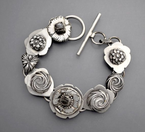 A beautiful sterling silver bracelet with dreamy hand fabricated sterling silver flowers. Two flowers have bezel set natural raw cubic diamond crystals. Lovely on the wrist and really heavy silver......quite substantial.