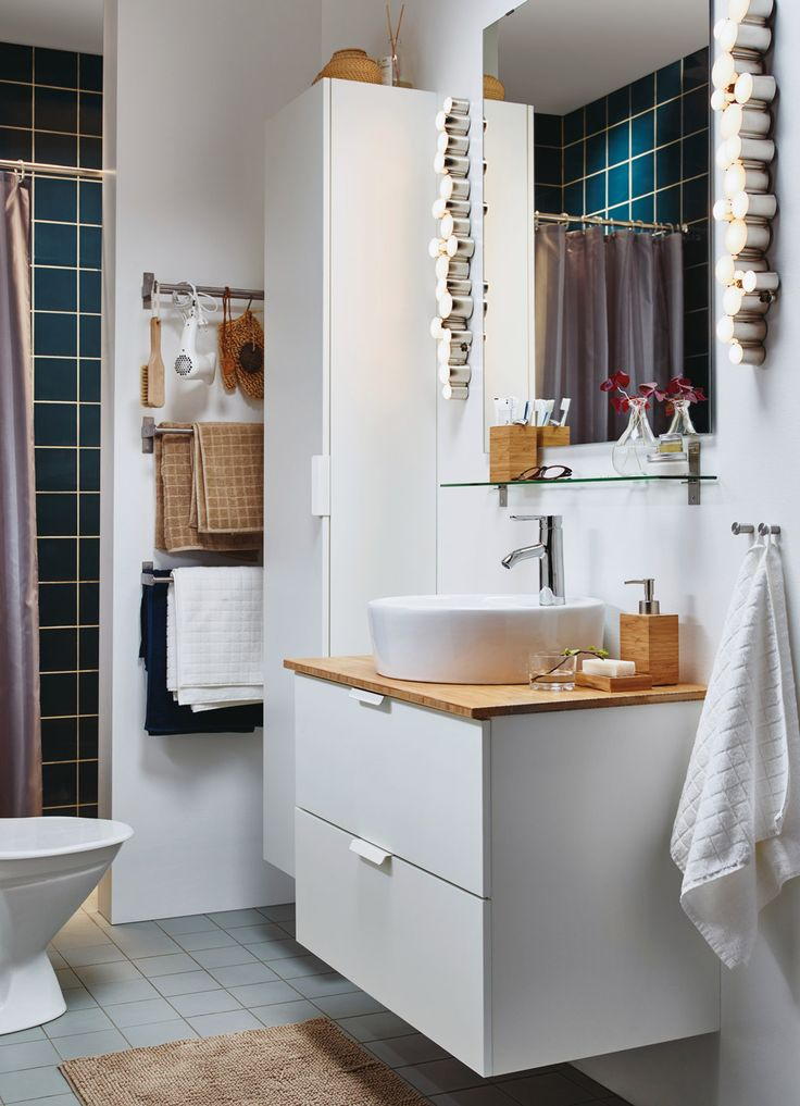 A small white bathroom with a high cabinet and a washstand combined with accessories in bamboo.