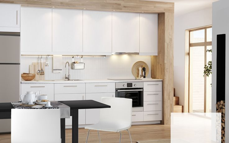 Modern white design kitchen with white cabinets, white ash RÅSDAL fronts, white worktops and integrated appliances
