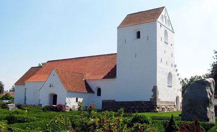Brovst Kirke med bautastenen i forgrunden; den er mindesten over de faldne fra sognet i de slesvigske kirke og den siges at være kastet efter kirken af Gjøltrolden for lægge den øde, da kirkeklokkerne generede trolden.