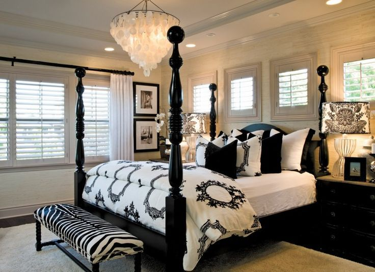 Interior Design by Barclay Butera. Black and white bedroom with damask lamp, zebra ottoman, four post bed, and Capiz Shell Chandelier.