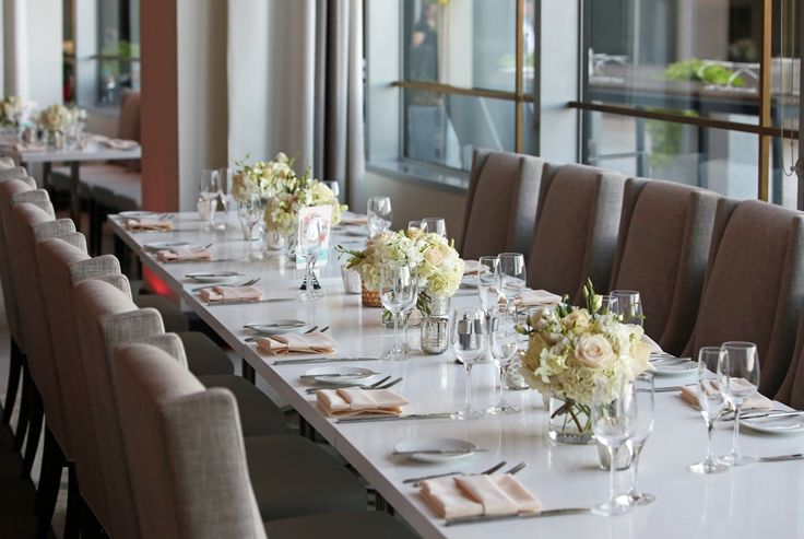 ivory low and lush centerpieces on white tabletop in Amuse Restaurant
