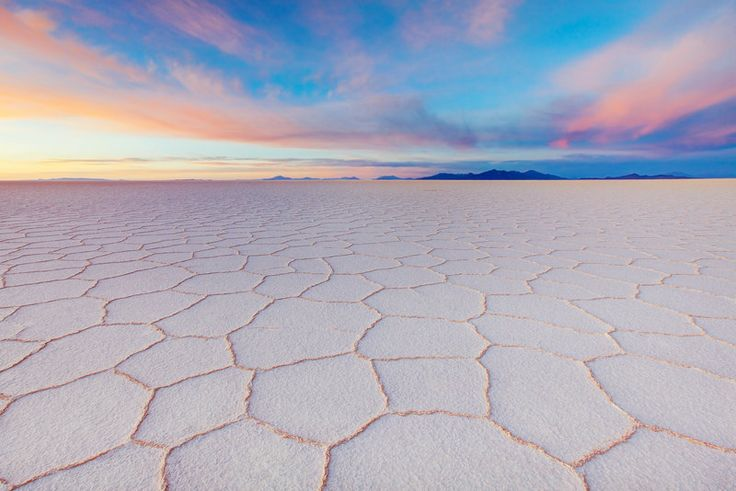 Sunrise over Salar de Uyuni - Dry and salty Salar de Uyuni is part of the Altiplano of Bolivia in South America. The Altiplano is a high plateau. The plateau includes fresh and saltwater lakes as well as the salt flats