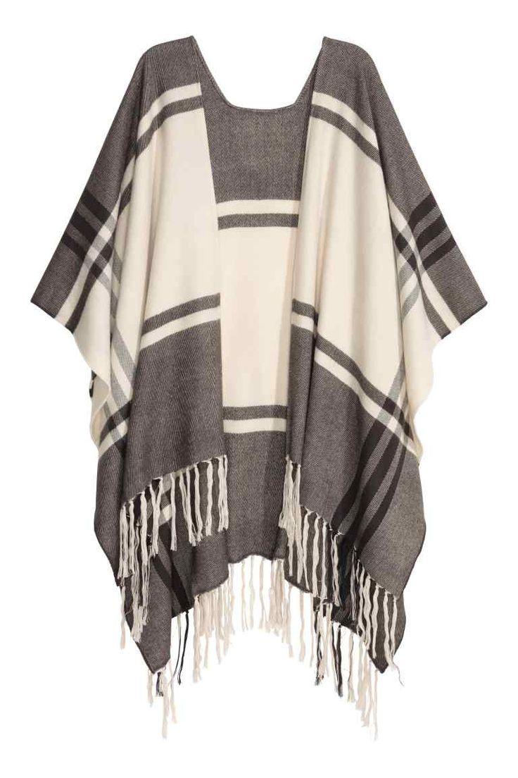 Poncho em tecido jacquard: Poncho em tecido jacquard macio com franjas no remate da base. Largura: 105 cm. Comprimento de costas: 74 cm.