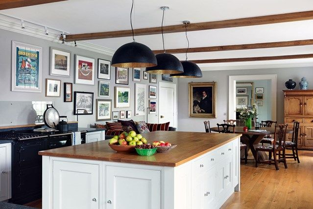 Modern country kitchen with Shaker-style island in Kitchen Design Ideas. A modern, white country kitchen hung with art collection above Aga, exposed beams and oak table.