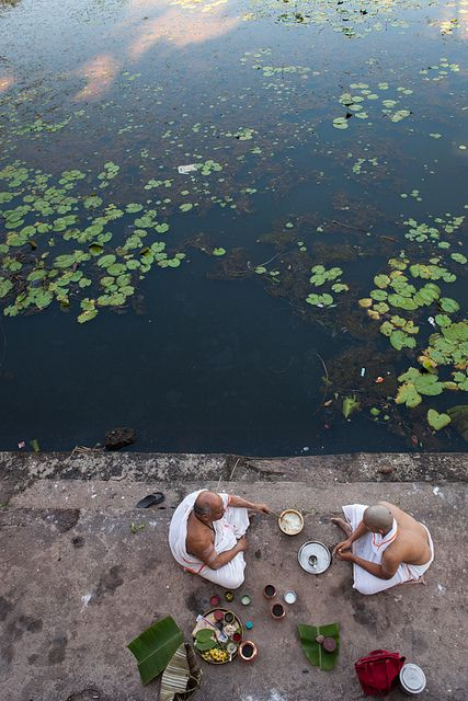 Hindu priest and a pilgrim during a puja ritual by the Koti Tirtha holy lake in Gokarna, Karnataka, India