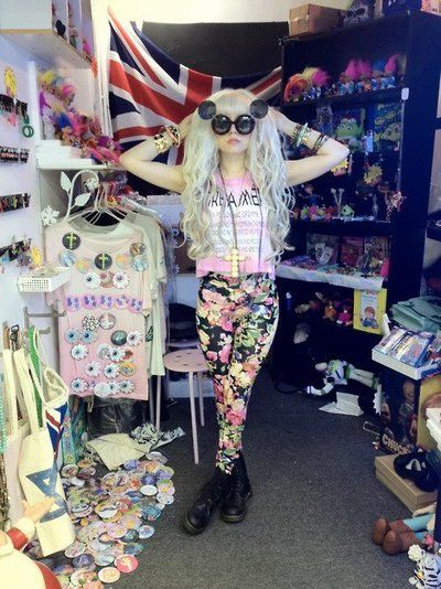 Love this overboard Pastel goth look with floral leggings, dark high boots, pastel blue hair, dark flip sunglasses.
