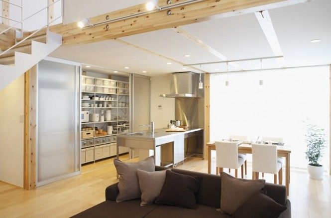 The kitchen is open plan with practical storage that can either be hidden behind frosted glass sliding doors, or revealed fully for easy access to pantry stores and kitchen tools.