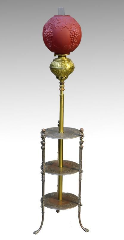 We are pleased to be offering today this adjustable height piano lamp that came out of a Connecticut estate. Three female figures hold up the top shelf of the triple shelf base. The base is