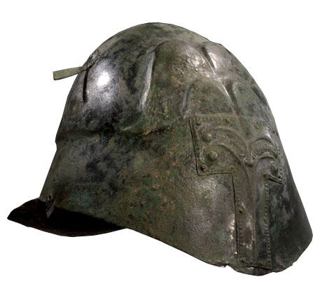 Apulian-Corinthian helmet 6th/5th century B.C. Undecorated. It appears that the formerly open eyes and front have been covered over with a bronze sheet. Probably a votive offering. Private collection