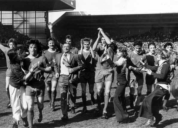 Liverpool manager Bob Paisley leads his team on a lap of honour to salute the Kop followign their victory over Queens Park Rangers at Anfield to secure the League Division One championship. Kevin Keegan and Emlyn Hughes are mobbed by girls who invaded the pitch.26th April 1975.