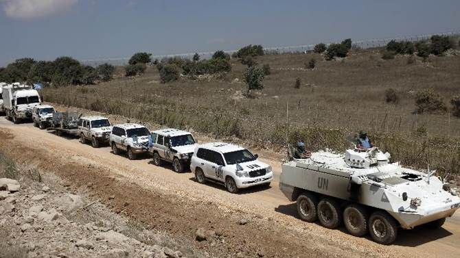 A convoy of United Nations Disengagement Observer Force (UNDOF) vehicles is seen as it leaves the Syrian side of the Golan Heights into the Israeli-occupied side of the strategic plateau, on September 15, 2014