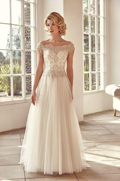 A soft A-Line gown featuring off the shoulder embellished lace and tulle.  <strong>Size: </strong>8 – 30 <strong>Colour: </strong>Oyster<strong> / </strong>Ivory <strong>Fabric:</strong>  Embellished lace, tulle <strong>Style:</strong> Soft A Line <strong>Neckline:</strong> Off the shoulder <strong>Laced or Zipped: </strong>Zipped
