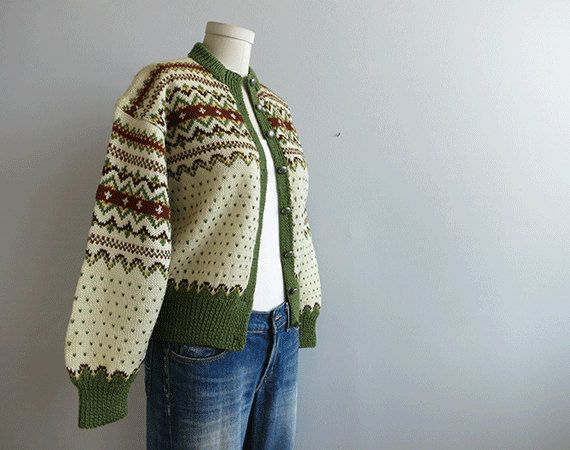 Buying a vintage fair isle sweater is like buying an instant heirloom. They are infinitely warm and knit to last well beyond your lifetime. This lovely handknit wool cardigan is done up in a warm indian summer palette of cream, olive green, russet and pale gold. Fair isle yoke pattern with a green birdseye pattern throughout. Eight pewter snowflake buttons dot the front. Chunky rib at the neck, cuff and bottom band. Super duper cozy!    Label: None available    Condition: Excellent to Mint…