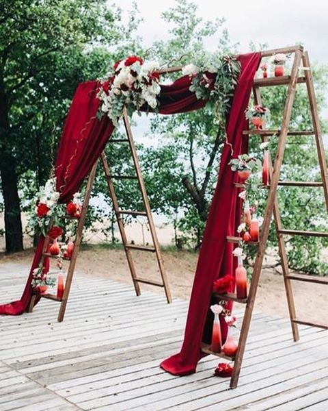 Two ladders lined with small vases of flowers are joined together by dramatically draped red velvet, setting the stage for this wedding's ceremony