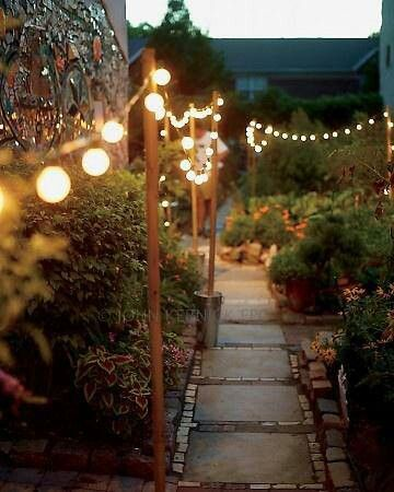Thin posts (tiki torches) along walkway with round lights or chinese lantern style stringers between.
