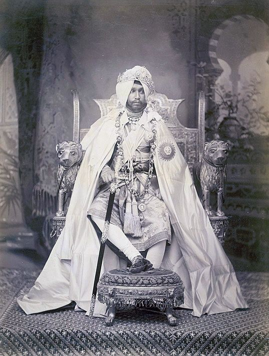 Sir Rajendra Singh, the Maharaja of Patiala, taken by an unknown photographer in c.1898. This full-length portrait shows the Maharaja seated on a gilded throne with his right leg raised on a footstool and holding a sword. He wears royal regalia including a cloak and a chain of office. The arms of the throne are designed in the form of lions, and it is set against a painted studio backdrop. The Maharaja (1872-1900) ruled the princely state of Patiala in Punjab from 1876 until his death.