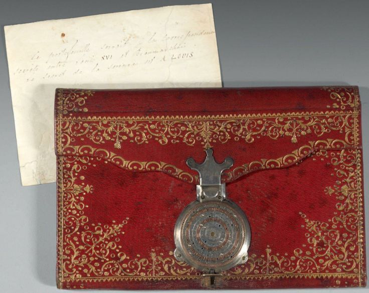 """Wallet belonging to Louis XVI, used for secret correspondence with secret agent Beaumarchais. Red morocco leather, gilt shackled foliage; inside covered with green silk. Combination lock in white and pink gold, composed of six circular dials engraved with letters. To open, align the letters """"A - L - O - U - I - S"""" from the center. Beaumarchais oversaw covert supply of arms and financial assistance before France's formal entry into the American War of Independence in 1778."""