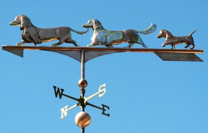 """Our TripleDachshund Dog Weathervane is crafted from copper sheetin theswell bodied style withglass eyes and distinctive toolingthat conveys the fur and gives the dogs a more realistic appearance. The """"Doxies"""" pictured here are a portrait piece. We worked from photos and with our customersto capture the essence of their sweet 'pack'. During the course of …"""