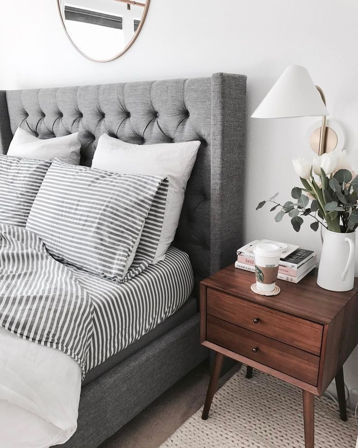 dream bedroom set of a gray tufted upholstered headboard and side panels, striped sheet set with white duvet and euro pillows. midcentury modern wood side table and wall sconces above for reading lights