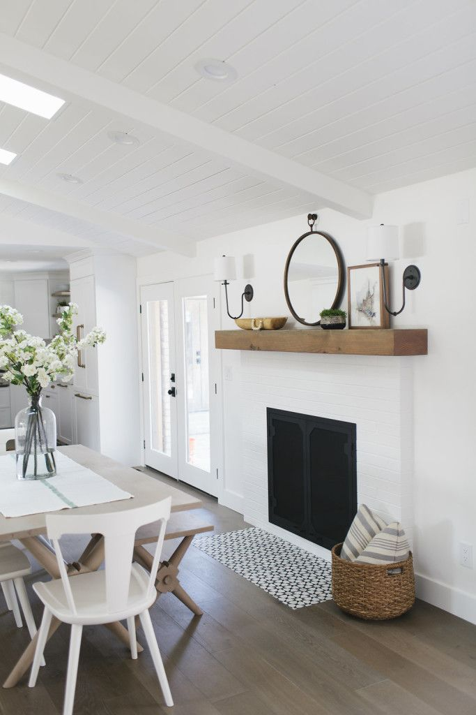 Possible fireplace in kitchen next to large doors and with shelf above. Simple white room