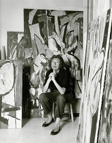 """Lee Krasner in her studio in 1956, two weeks after husband Jackson Pollock's death. Visible are her """"Prophecy"""" (right) and """"Cauldron"""" (unfinished, behind)."""