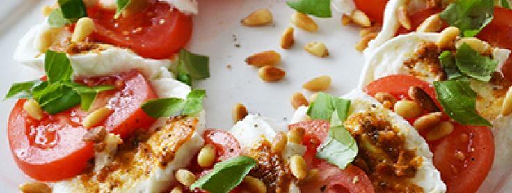2 bolletjes mozzarella 3 tomaten Handje verse basilicum 25 gram pijnboompitjes Scheutje olijfolie 1 el pesto Grove zwarte peper