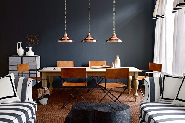 Decorating with dark paint doesn't mean you'll end up with a room of Stygian gloom. In fact the very opposite. Used properly drama and atmosphere await. Like this dining room which combines black walls with copper highlights.
