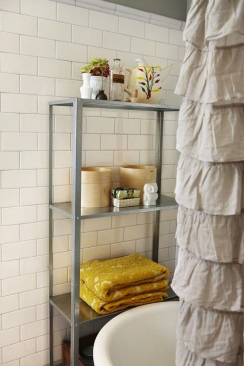 Amazing vintage bathroom with gray walls paint color, subway tiles backsplash, claw foot tub, Urban Outfitters Waterfall Shower Curtain in gray and Ikea Hyllis Shelving Unit and mustard yellow damask towels.