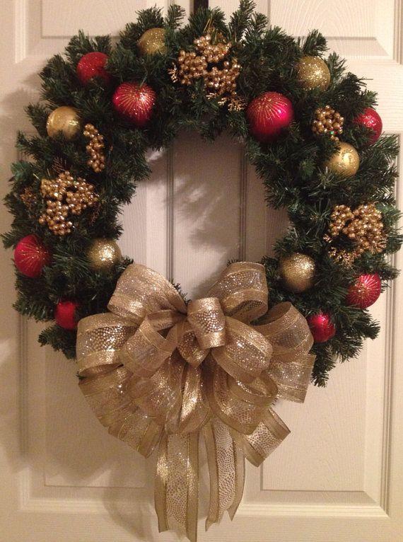 Esta corona de pino artificial es medida 24 . Se decoran con diversos colores y texturas de adornos rojos y dorados y un impresionante arco de color oro. Póngase en contacto conmigo si usted tiene cualquier pregunta
