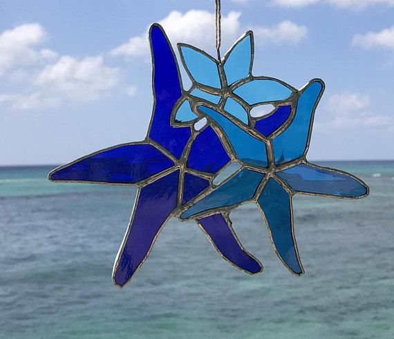 Starfish Stained Glass Sun Catcher is a sweet little family from the sea. Made from an assortment of domestic and imported stained glass in the copper foil method. This freeform piece is reinforced with copper wire around the outer edge for strength. Starfish and sea shell do not